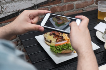 Close up, man takes photo of food with mobile phone at an outdoor bar.  Taking a picture of your food with your phone. Hamburger, fries, and beer on white plate outside on a black table focus on food