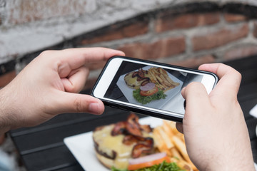 Man takes photo of food with mobile phone at an outdoor bar.  Taking a picture of your food with your phone. Hamburger, fries, and beer on a white plate outside on a black table, point of view shot.