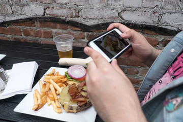 Man holding a mobile phone taking a photo of his food. Smartphone food photography. Taking a picture of hamburger, beer, and french fries at an outdoor bar with a mobile phone.