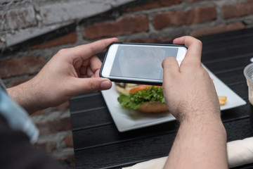 Man holding a mobile phone taking a photo of his food. Smartphone food photography. Taking a picture of hamburger and french fries at an outdoor pub.