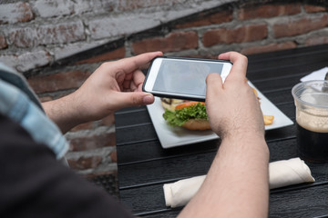 Man takes a photo of his dinner with his cell phone. Mobile phone photography. Taking a photo with phone of hamburger, french french fries and dark beer on white plate on black table outside.