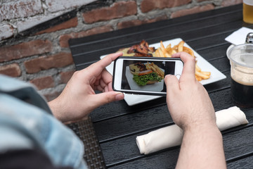 Man takes a photo of his lunch with his cell phone. Mobile phone photography. Taking a photo with phone of hamburger, french french fries and dark beer on white plate on black table outside.