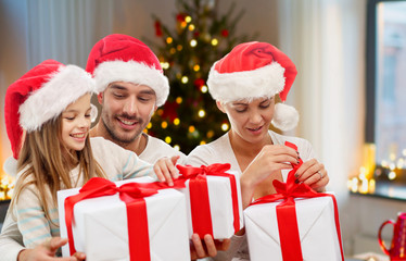 christmas, holidays and family concept - happy mother, father and daughter in santa hats with gifts sitting on couch at home