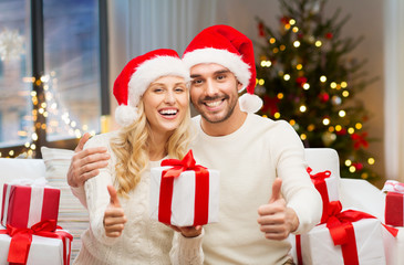 holidays and people concept - happy couple in santa hats with gift boxes showing thumbs up at home over christmas tree lights background
