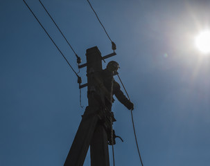 electrician worker on a pole with wires, electricity repair works