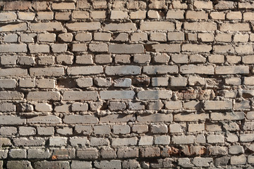 Old yellow brick wall weathered by time