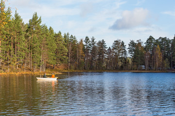 Fishing from a rowing boat in a forest lake