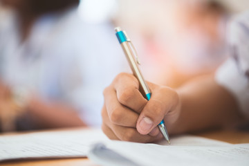 School students taking exam writing answer in classroom with stress