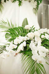 Elements of wedding decorations in a tropical style. Boudoir decorations with tropical leaves and white orchids, roses, feces and candles