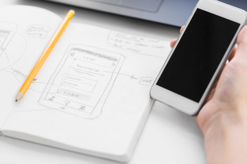 app design, technology and business concept - hand of web designer or developer with smartphone and sketch of user interface in notebook at office