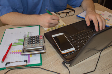 Male working with calculator, business document and laptop computer notebook