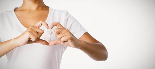 Women making heart shape with their fingers around pink ribbon