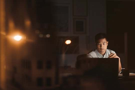 Young Asian businessman working alone in his office at night