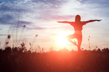Young woman silhouette yoga on nature at sunset. Fresh air, healthy lifestyle, copy space. Magic background