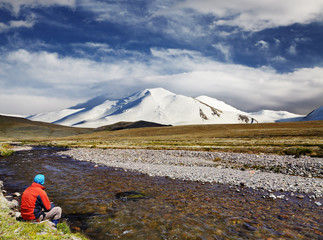 Fototapete - Man sitting alone on the river bank against snowy mountain and blue sky background