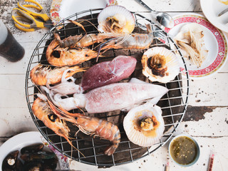 Seafood BBQ with shimps, squid, shell and mussel grilling on chacoal stove close up.