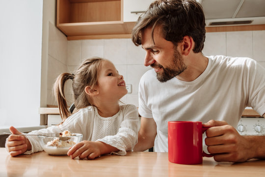 Family. Food. Parenthood. Dad and his little daughter are talking and smiling while having a breakfast in the kitchen at home