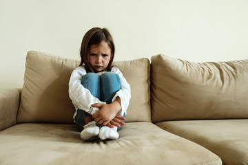 Childhood. Lonelyness. Offended little girl is hugging her knees and looking at camera while sitting alone on a couch at home