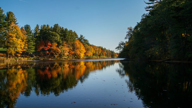 Beautiful scene of the autumn colorful trees reflected in the water of a river during fall season in Massachusetts