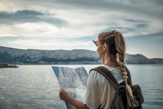 Hiker woman with map looking at sea bay while traveling