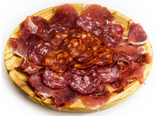 Typical spanish food with ham and sausage on a wooden plate