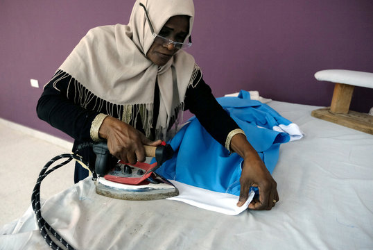 A woman irons clothes in a sewing workshop supervised by a charity to help widows, divorcees and needy in Benghazi