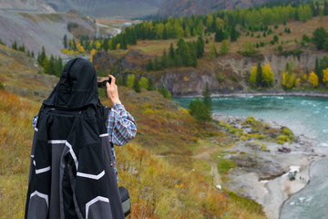 adult man, tourist, standing on a hill takes pictures on smartphone autumn mountain landscape and turquoise river