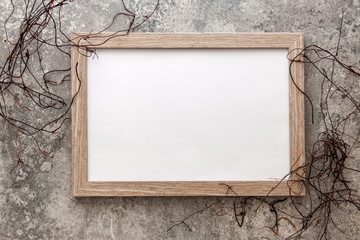 Wooden frame mockup on a background of old concrete with dried vines