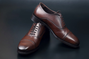 Classic men's brown Oxford shoes on dark background