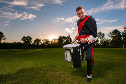 Cool portrait of musician in uniform with atmospheric light on a green grass field at sunset