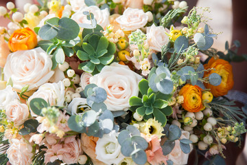Bride`s wedding bouquet with roses befor wedding ceremony. Beautiful flowers background are pink, orange, white, yellow, green, cream.
