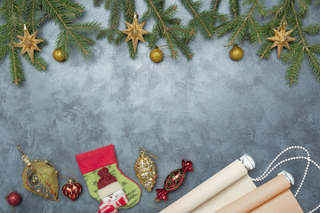 The rolled color shutters is on a concrete background. Color roller blinds lie on gray background.  Christmas decorations on blue dark stucco concrete background with fir branch.