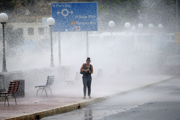 Woman gets caught in a cloud of sea spray and water as strong winds and rough seas batter the coast of the Maltese islands, in St Paul's Bay