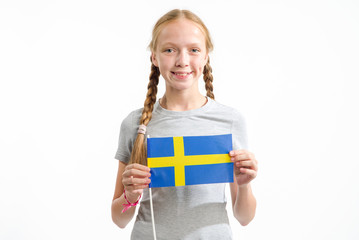 Beautiful teen girl with the flag of Sweden on a light background. Learn Swedish.