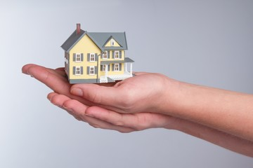 Cupped Hands Holding a Model of a House on Grey Background