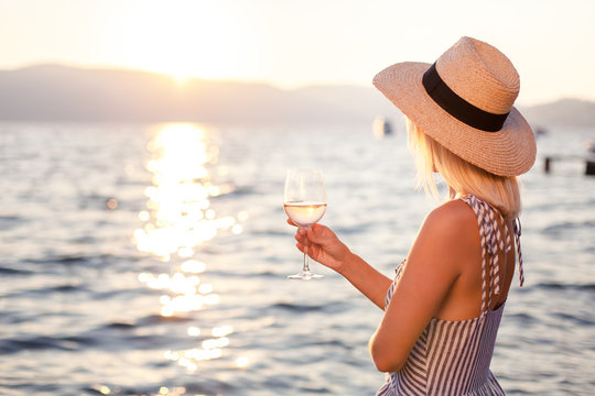 Woman holds wineglass at background of sunset sea or ocean. Blond girl is wearing in casual striped dress, straw hat. Beautiful woman is relaxing, traveling and enjoying life in summer vacation.