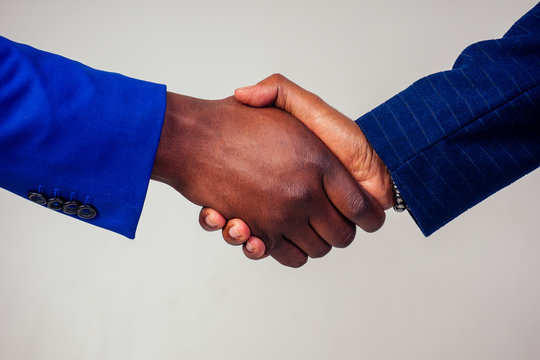 Portrait of two businessmen shaking hands in a business meeting on white background in studio shot