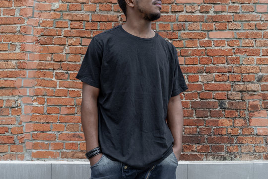 Close up of dark-skinned man in black blank T-shirt on bricked background.