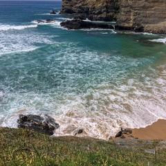 seascape, waves roll on a sandy beach, fine sunny day, sea foam, rocks