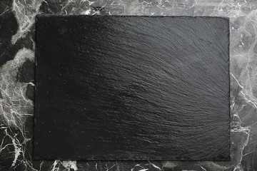 Black textured slate board on marble background
