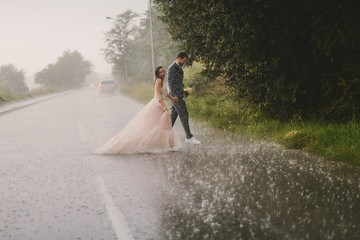 Silly young just married couple crossing road on rainy day. Walking in wet ceremonial clothes.