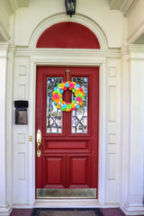 Resentails red front door with leaded glass in white house colorful Day of the Dead Halloween wreath