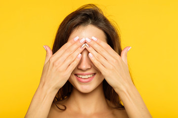 hide and seek. facial expression. emotional portrait. smiling joyful jolly woman covering eyes with hands. young beautiful brown haired girl on yellow background. Wall mural