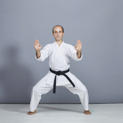 Young athlete with a black belt performs a formal karate exercise on a gray background