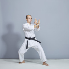 A man performs formal karate exercises on a gray background