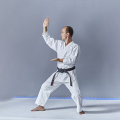 A man in karategi trains a formal karate exercise on a gray background