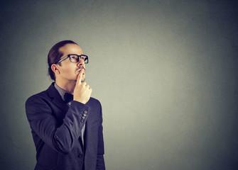 Doubtful serious man looking up in wonders
