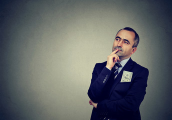 Pensive middle-aged businessman looking away