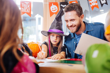 Father with children. Handsome loving father joining his children wearing costumes drawing Halloween pictures
