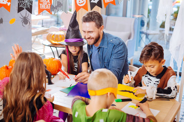 Painting bats. Smiling handsome bearded father helping his children painting bats and spiders for Halloween